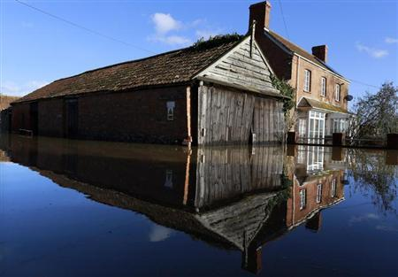 A house is reflected in an urban landscape taken in the flooded Somerset village of Moorland February 16, 2014. British ministers will meet representatives of the insurance industry on Tuesday, February 18, who will brief them on their progress in dealing with victims of winter floods across southern England. REUTERS/Cathal McNaughton