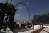 A worker guides a steel arch being lifted by a crane into place overtop the damaged cupola, as part of a frame that will support a temporary metal roof, in the early stages of reconstruction work at Nuestra Senora de Los Angeles (Our Lady of Angels) church, three years after an earthquake collapsed nearly half of its 18th-century dome, in Mexico City, Wednesday, Sept. 23, 2020. The dome didn't collapse at the moment of the quake, but rather five days later, leaving time to get people and precious objects out. (AP Photo/Rebecca Blackwell)