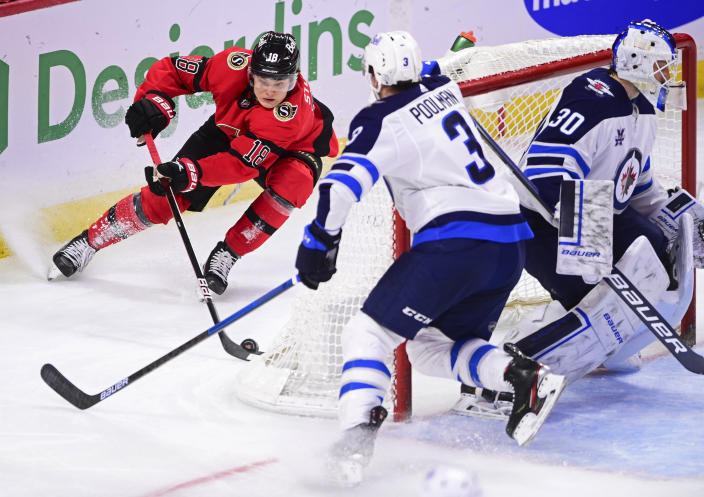 Ottawa Senators' Tim Stutzle (18) stops behind the net of Winnipeg Jets goaltender Laurent Brossoit (30) as Jets' Tucker Poolman (3) defends during the second period of an NHL hockey game Wednesday, April 14, 2021, in Ottawa, Ontario. (Sean Kilpatrick/The Canadian Press via AP)