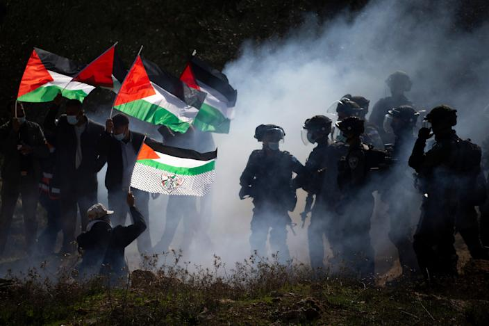 <p>Israeli border police officers and Palestinians clash during a protest against the expansion of Israeli Jewish settlements near the West Bank town of Salfit in December</p> (AP)