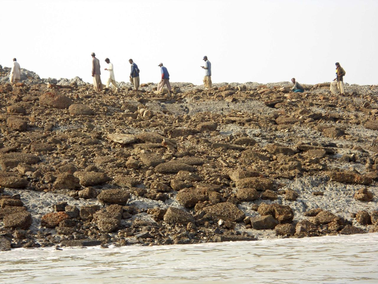 People walk on an island that rose from the sea following an earthquake, off Pakistan's Gwadar coastline in the Arabian Sea September 25, 2013. A major earthquake hit a remote part of western Pakistan on Tuesday, killing at least 45 people and prompting the new island to rise from the sea just off the country's southern coast. The earthquake was so powerful that it caused the seabed to rise and create a small, mountain-like island about 600 meters off Pakistan's Gwadar coastline. Television channels showed images of a stretch of rocky terrain rising above the sea level, with a crowd of bewildered people gathering on the shore to witness the rare phenomenon. REUTERS/Stringer (PAKISTAN - Tags: ENVIRONMENT DISASTER TPX IMAGES OF THE DAY)