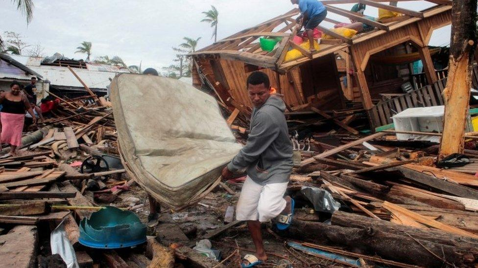 Residents recover a mattress from the debris of their house in Puerto Cabezas, Nicaragua