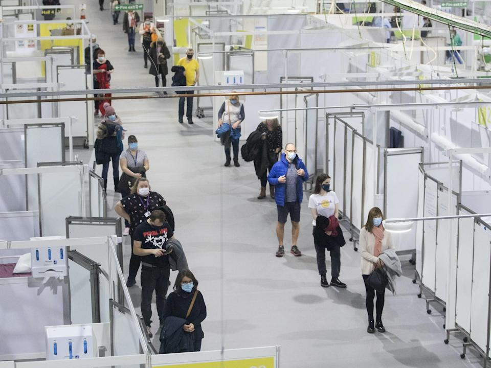 <p>People queue for the Covid vaccine at SSE Hydro in Glasgow</p> (PA)