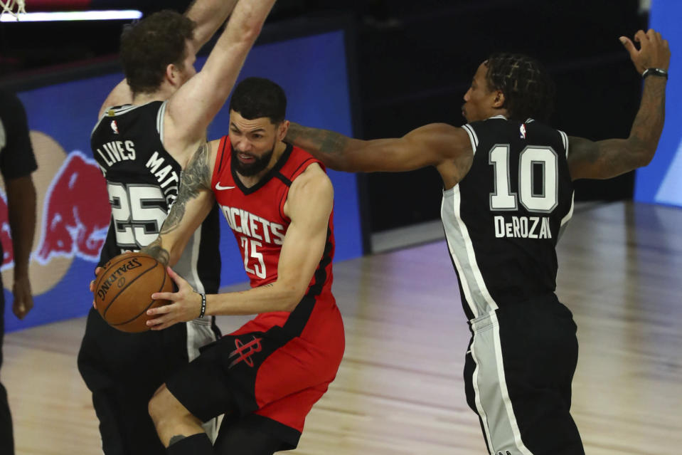 Houston Rockets guard Austin Rivers (25) drives to the basket while San Antonio Spurs center Jakob Poeltl (25) and forward DeMar DeRozan (10) defend during the second half of an NBA basketball game Tuesday, Aug. 11, 2020, in Lake Buena Vista, Fla. (Kim Klement/Pool Photo via AP)