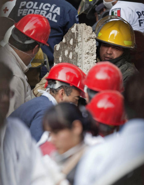 An emergency responder carries a piece of concrete as emergency workers and firefighter dig for survivor at the site on an explosion at an adjacent building to the executive tower of Mexico's state-owned oil company PEMEX, in Mexico City, Thursday Jan. 31, 2013. The explosion killed more than 10 people and injured some 80 as it heavily damaged three floors of the building, sending hundreds into the streets and a large plume of smoke over the skyline. (AP Photo/Eduardo Verdugo)
