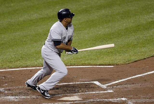 New York Yankees' Vernon Wells singles in the third inning of a baseball game against the Baltimore Orioles, Thursday, Sept. 12, 2013, in Baltimore. Alfonso Soriano and Alex Rodriguez scored on the hit. (AP Photo/Patrick Semansky)