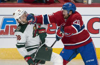 Minnesota Wild's Ryan Hartman gets a glove in the face from Montreal Canadiens' Jeff Petry during first-period NHL hockey game action in Montreal, Thursday, Oct. 17, 2019. (Paul Chiasson/The Canadian Press via AP)
