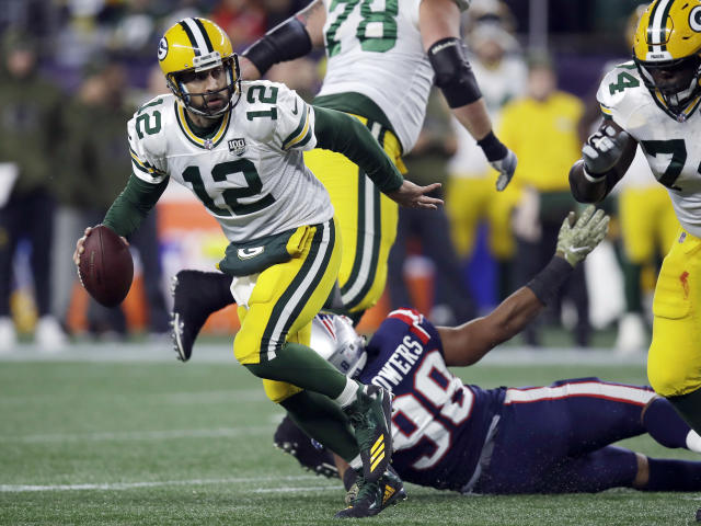 FILE - In this Sunday, Nov. 4, 2018, file photo, Green Bay Packers quarterback Aaron Rodgers (12) scrambles away from New England Patriots defensive end Trey Flowers (98) during the first half of an NFL football game in Foxborough, Mass. The Packers are hoping to bounce back from losses to the Rams and Patriots when they host the Miami Dolphins on Sunday(AP Photo/Charles Krupa, File)