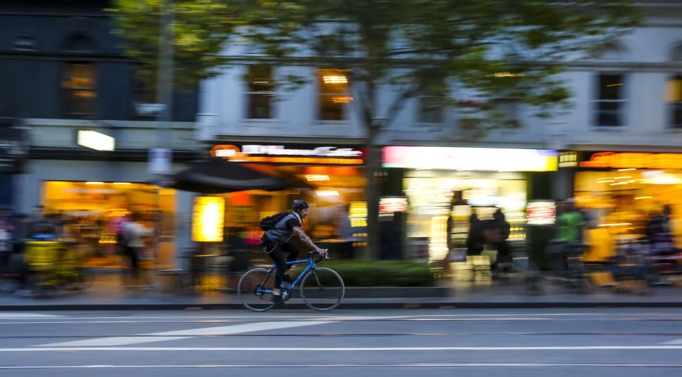 MELBOURNE, AUSTRALIA - MARCH 15, 2018 : Cyclist at Melbourne city center. People using bicycle for commute to work or food delivery.
