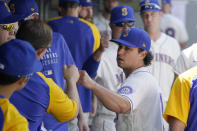 Seattle Mariners starting pitcher Marco Gonzales, right, is greeted in the dugout after he was pulled during the sixth inning of a baseball game against the Oakland Athletics, Sunday, July 25, 2021, in Seattle. (AP Photo/Ted S. Warren)