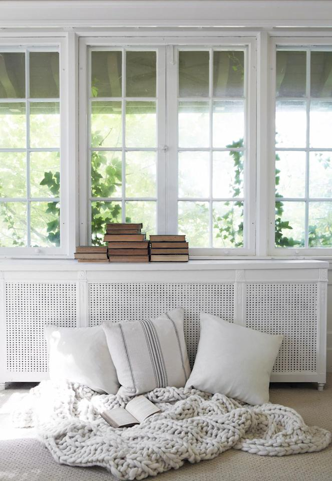 """<p><a href=""""https://leanneford.com/"""" target=""""_blank"""">Leanne Ford Interiors</a> built a cabinet over this radiator to reclaim the hallway space and turn it into a beautiful little reading nook. Now, instead of clashing with the country chic home, it's trellised grill front complements the laidback style beautifully. </p>"""