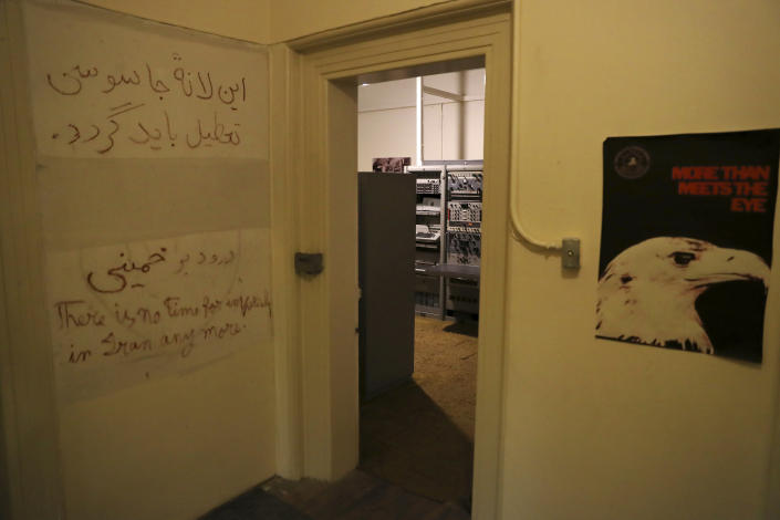 """In this Sept. 26, 2019 photo, anti-U.S. slogans are written on the wall of a corridor of the former U.S. Embassy, now partly a museum, in Tehran, Iran. Slogans in Persian read: """"The den of espionage should be shut down"""" and another line honors Ayatollah Ruhollah Khomeini who became supreme leader of Iran after returning from exile in France earlier in 1979. The slogan in English reads: """"There is no time for intervention in Iran anymore."""" (AP Photo/Vahid Salemi)"""