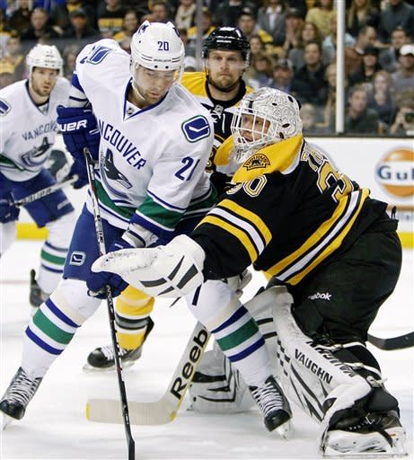 Boston Bruins' Tim Thomas (30) makes a save in front of Vancouver Canucks' Christopher Higgins (20) in the first period of an NHL hockey game in Boston, Saturday, Jan. 7, 2012. (AP Photo/Michael Dwyer)