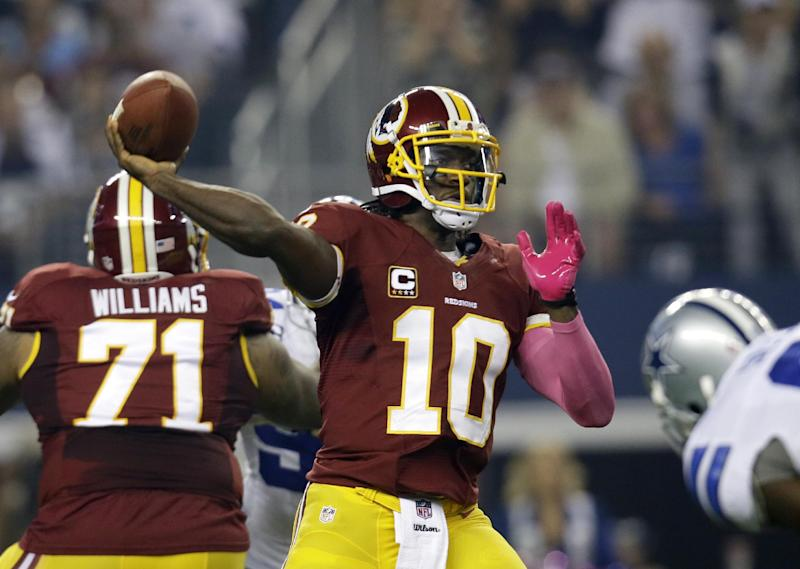 Washington Redskins quarterback Robert Griffin III (10) prepares to pass as Trent Williams (71) provides coverage against pressure from the Dallas Cowboys in the first half of an NFL football game, Sunday, Oct. 13, 2013, in Arlington, Texas. (AP Photo/Tim Sharp)