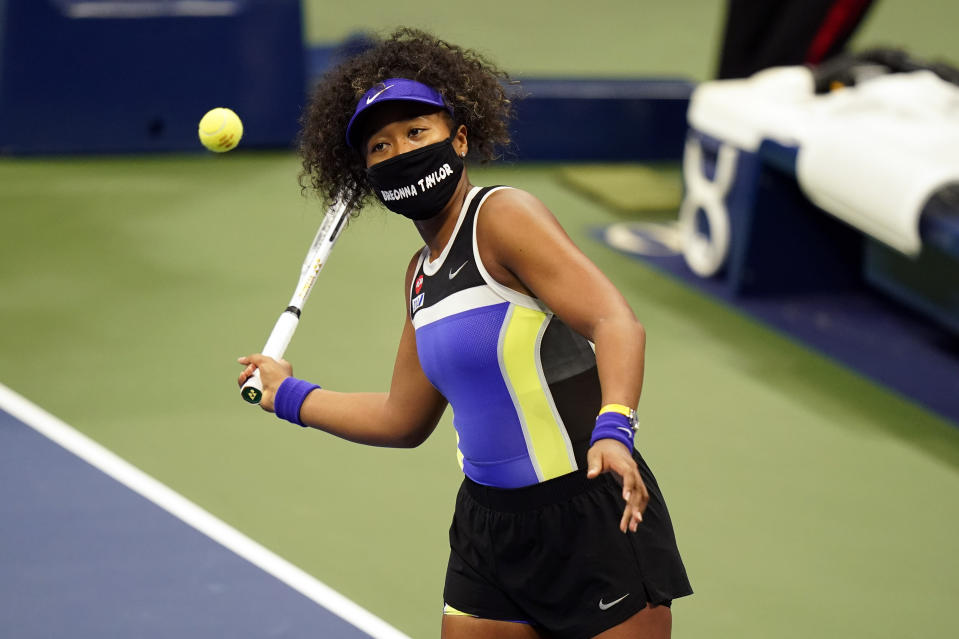 Naomi Osaka in a black Breonna Taylor mask about to hit a tennis ball.