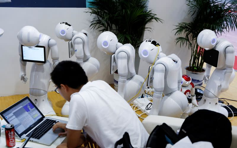 """FILE PHOTO: A man programs SoftBank Robotics """"Pepper"""" robots at the 2017 World Robot Conference in Beijing"""