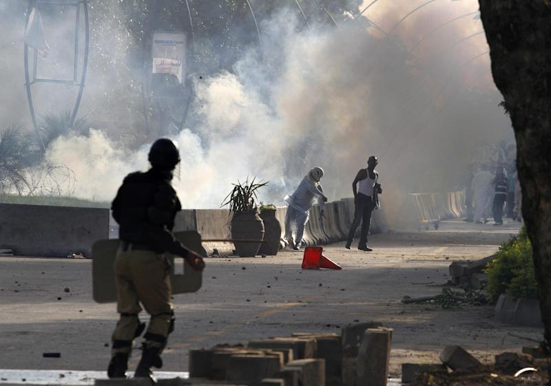 A Pakistani protestor hurls back a tear gas canister fired by police during clashes that erupted as protestors tried to approach the U.S. embassy, Friday, Sept. 21, 2012 in Islamabad, Pakistan. Protests by tens of thousands of Pakistanis infuriated by an anti-Islam film descended into deadly violence on Friday, with police firing tear gas and live ammunition in an attempt to subdue rioters who hurled rocks and set fire to buildings in some cities.  Four people were killed and dozens injured on a holiday declared by Pakistan's government so people could rally against the video. (AP Photo/Anjum Naveed)
