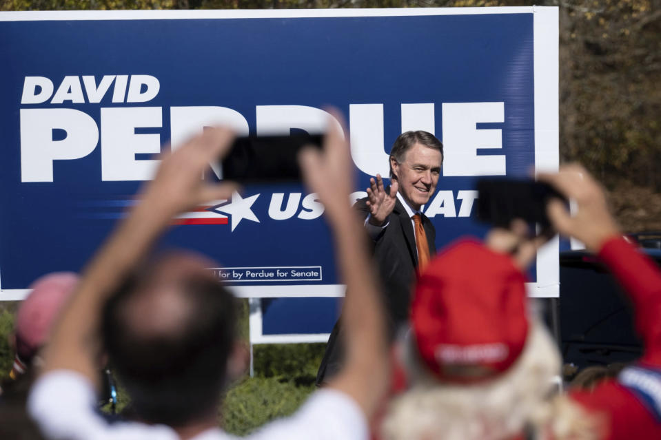 FILE - In this Nov. 20, 2020, file photo Sen. David Perdue, R-Ga., takes the stage before Vice President Mike Pence during a Defend the Majority Rally in Canton, Ga. (AP Photo/Ben Gray, File)