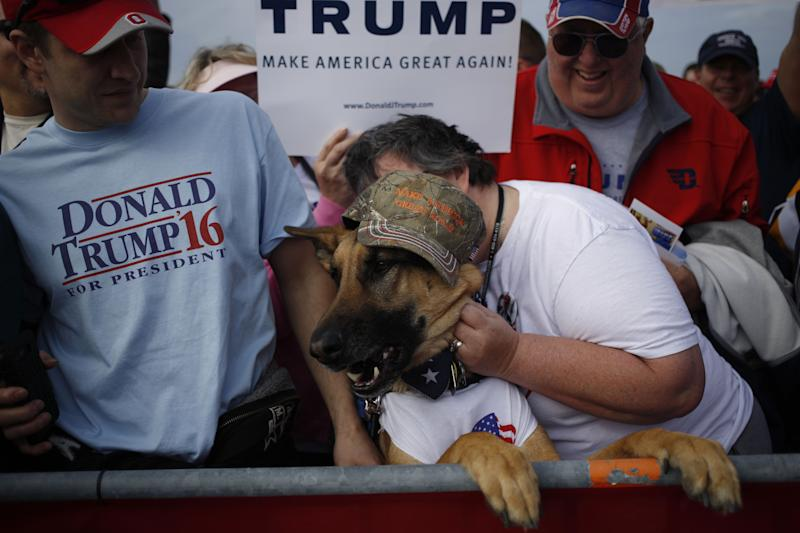 People and a German shepherd wait for the start of a campaign event for Donald Trump in Dayton, Ohio, on March 12, 2016.