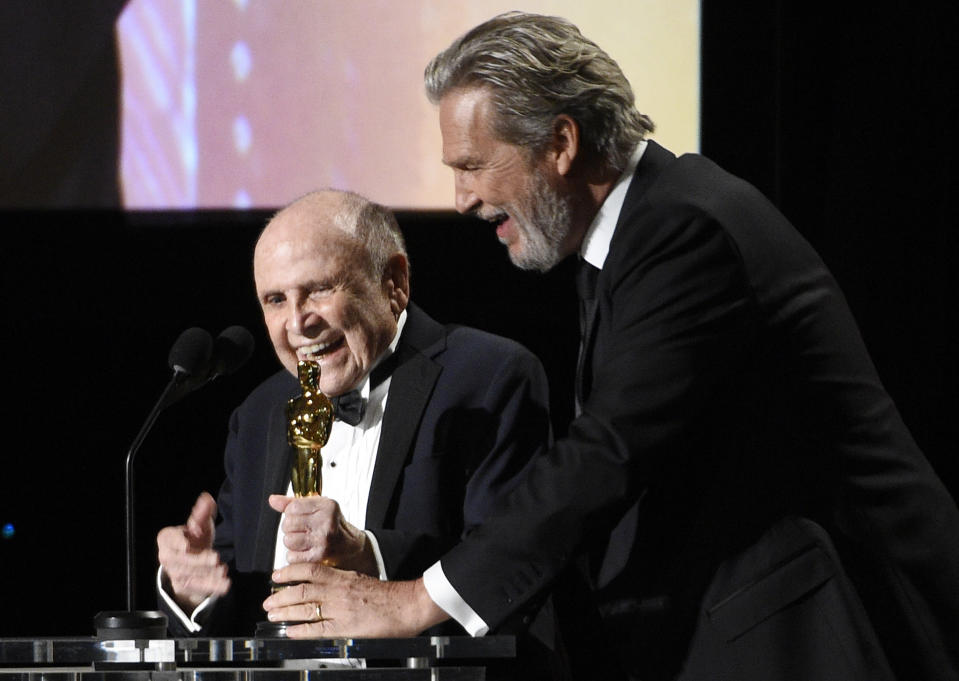 FILE - In this Saturday, Nov. 12, 2016 file photo, Honoree Lynn Stalmaster, left, collects his award from actor Jeff Bridges onstage at the 2016 Governors Awards at the Dolby Ballroom in Los Angeles .Lynn Stalmaster, the Oscar-winning casting director whose eye for talent helped launch the careers of John Travolta, Christopher Reeve, Richard Dreyfuss and many other actors, has died. He was 93. (Photo by Chris Pizzello/Invision/AP, File)