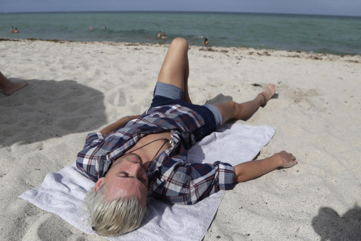Nivek Divincci lies on the beach at Haulover Park during the new coronavirus pandemic, Friday, June 19, 2020, in Miami. Warm weather beach destinations are the most popular vacation searches, with Florida, Myrtle Beach, S.C., San Diego and Key West, Fla., among the top considerations. (AP Photo/Lynne Sladky)