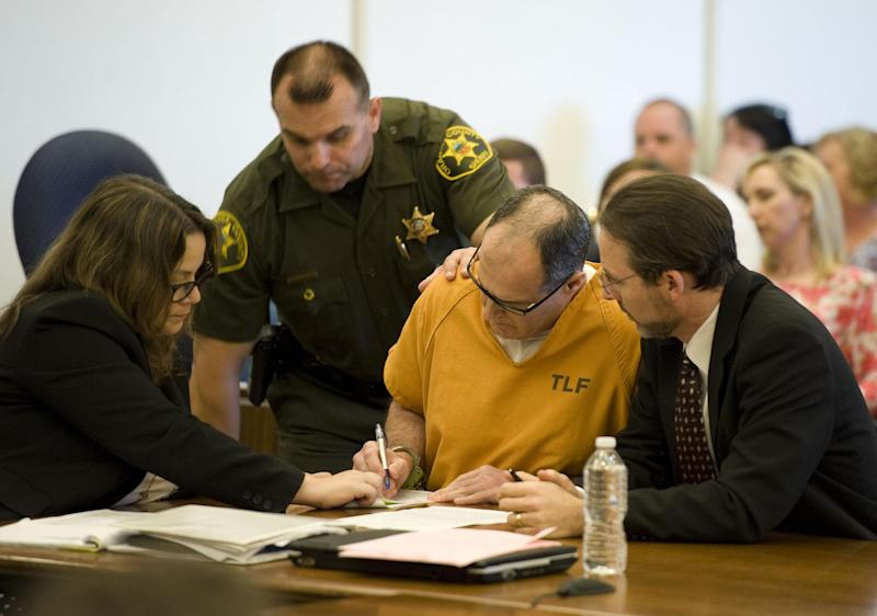 Scott Dekraai signs court documents with his public defenders Lisa Kopelman, left, and Scott Sanders looking on at Orange County Superior Court in Santa Ana, Calif., on Friday, May 2, 2014. Dekraai, 44, who was in a custody fight with his ex-wife pleaded guilty Friday to killing her and seven others in a shooting rampage at a California hair salon in 2011. Dekraai donned a bulletproof vest before heading to the Seal Beach salon where his ex-wife worked as a stylist in October 2011. Authorities said he shot and killed Michelle Fournier before turning his gun on the salon's owner and spraying Salon Meritage with bullets. The salon reopened about a year later, with six of the original employees returning to work. (AP Photo/The Orange County Register, Kevin Sullivan) MAGS OUT; LOS ANGELES TIMES OUT