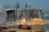 A picture taken on August 5, 2020 shows the damaged grain silo and a burnt boat at Beirut's harbour, a day after a powerful explosion tore through Lebanon's capital,when a huge depot of ammonium nitrate ignited at the city's main port