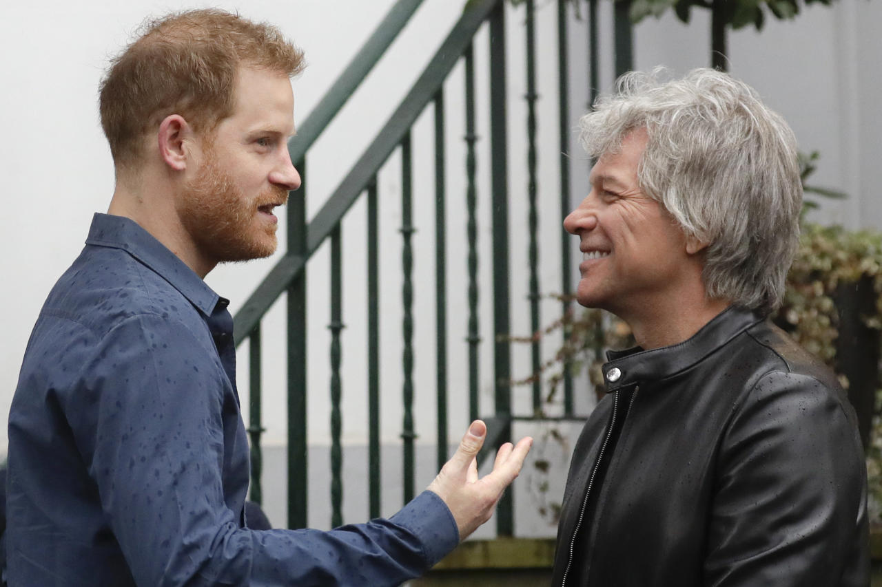Britain's Prince Harry, the Duke of Sussex, left, speaks to musician Jon Bon Jovi at Abbey Road Studios in London, Friday, Feb. 28, 2020. The Prince will meet musician Jon Bon Jovi and members of the Invictus Games Choir, who are recording a special single in aid of the Invictus Games Foundation. (AP Photo/Kirsty Wigglesworth)