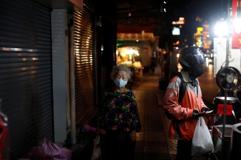 An elderly woman wearing a mask walks past a delivery man at an empty street during the coronavirus disease (COVID-19) outbreak, in Chinatown, Bangkok