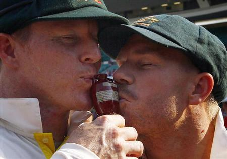 "Australia's Chris Rogers (L) and David Warner kiss the ""Replica Ashes Urn"" as they celebrate winning the fifth Ashes cricket test against England at the Sydney Cricket Ground January 5, 2014. REUTERS/David Gray/Files"