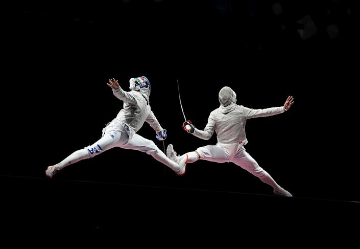 <p>Luca Curatoli of Italy (left) competes against Sanguk Oh of South Korea during the men's sabre team gold medal match on day five of the Games.</p>
