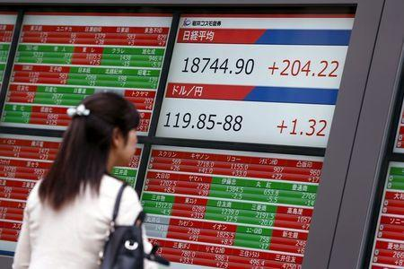 A woman looks at screens displaying, stock quotes, the Nikkei average and the Dollar to Yen exchange rate outside a brokerage in Tokyo, August 25, 2015. REUTERS/Thomas Peter