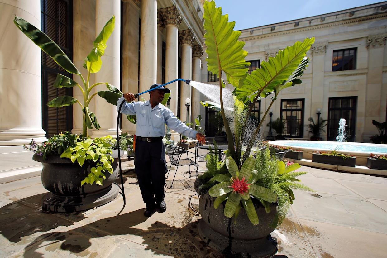 Daniel Agbleze waters flowers in one of the four inner courtyards at the Supreme Court in Washington, U.S. June 6, 2016.