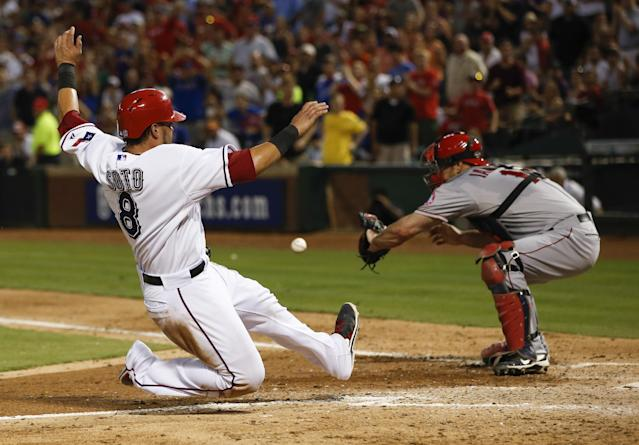 Texas Rangers' Geovany Soto (8) slides safely into home plate ahead of the throw to Los Angeles Angels catcher Chris Iannetta, right, during the third inning of a baseball game, Tuesday, July 30, 2013, in Arlington, Texas. (AP Photo/Jim Cowsert)
