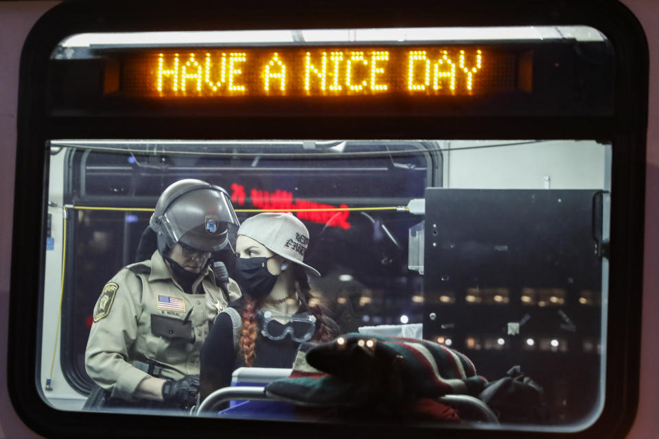 Arrested protesters are loaded onto a transport bus by police on South Washington Street, Sunday, May 31, 2020, in Minneapolis. (AP Photo/John Minchillo)