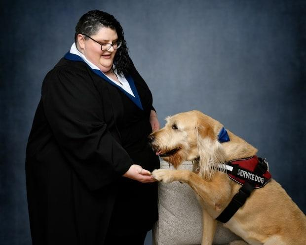 Levon Beck graduated with her high school diploma earlier this year through the adult learning program at the Nova Scotia Community College. She is pictured with her service dog, Thomas. (Applehead Studio/Submitted by Levon Beck - image credit)