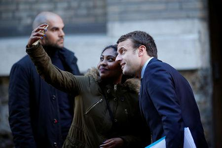 Emmanuel Macron, head of the political movement En Marche !, or Onwards !, and candidate for the 2017 presidential election, poses for a selfie as he leaves his home in Paris