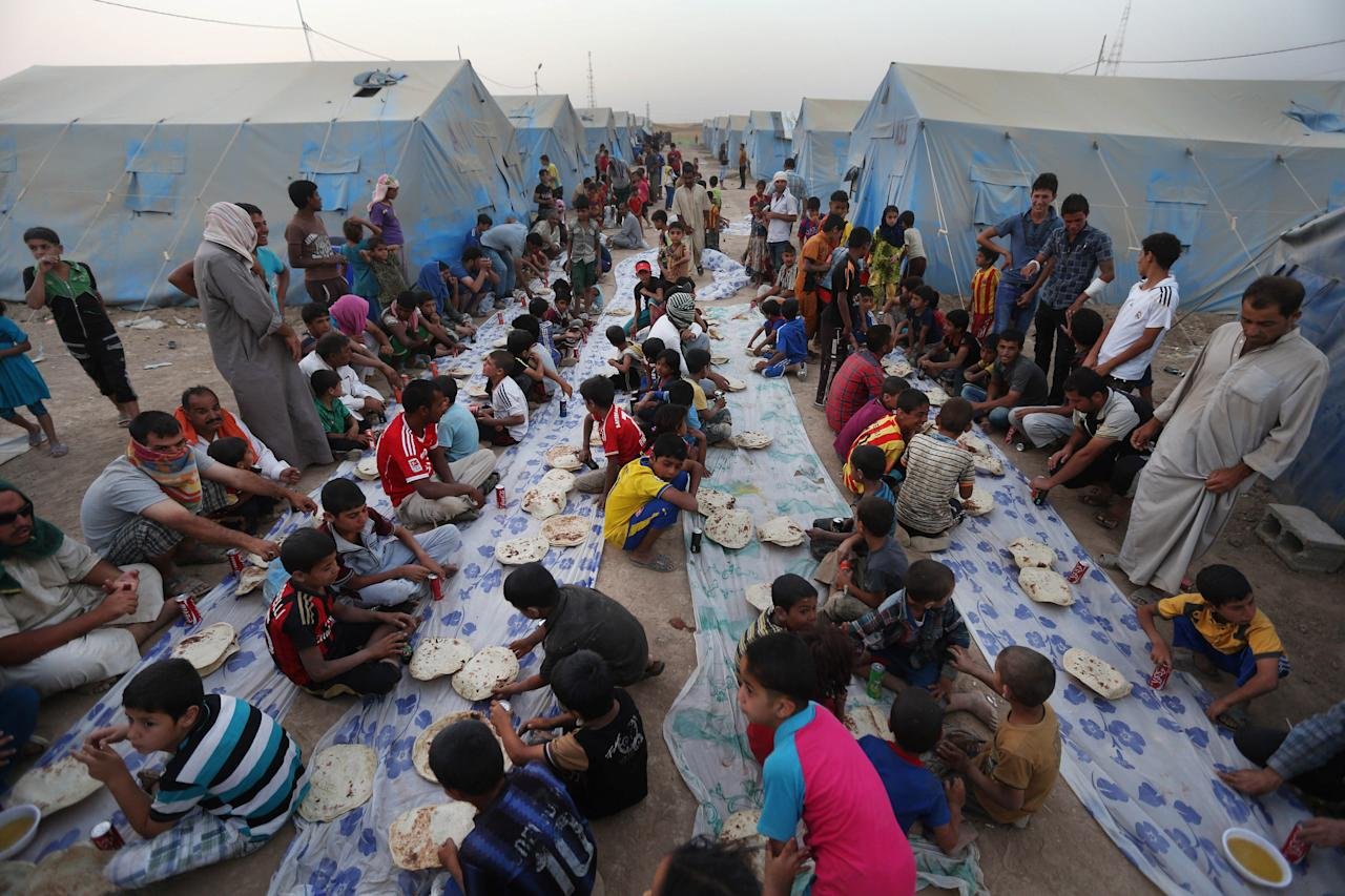 In this Sunday, June 29, 2014 photo, displaced Iraqi citizens gather for a communal meal to break their fast during the first day of the Islamic holy month of Ramadan, at an encampment for displaced Iraqis who fled from Mosul and other towns, in the Khazer area outside Irbil, northern Iraq. The grueling fast, in which believers abstain from water, food and cigarettes from sunrise to sunset, has been made even harsher for many living in dusty, hot tents. (AP Photo/Hussein Malla)
