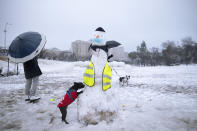 People walk their dogs next to a snowman decorated with a face mask in a snow-covered park, in Jerusalem, Thursday, Feb. 18, 2021. (AP Photo/Oded Balilty)
