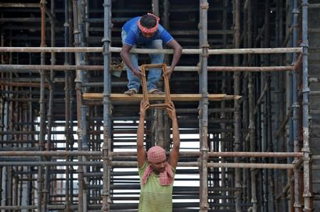 FILE PHOTO: Labourers work at the construction site of a residential building on the outskirts of Kolkata