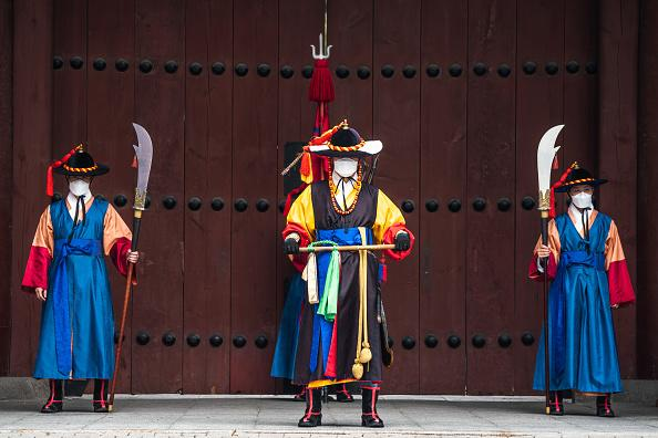 Guards of Deoksugung Palace in Seoul, South Korea, wearing face masks as a preventive measure stand at the gate of the palace.