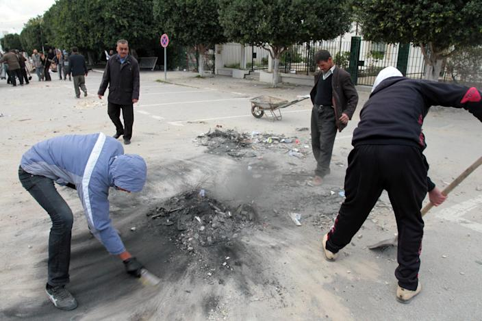 Local people clean damages in the street a day after clashes between protestors and riot police in Siliana, Tunisia, Sunday, Dec. 2, 2012. The Regional Workers Union in Siliana announced a provisional halt to the strike Sunday, hours after agreeing to a deal with the central government in Tunis, the capital of this North African nation. (AP Photo / Amine Landoulsi)