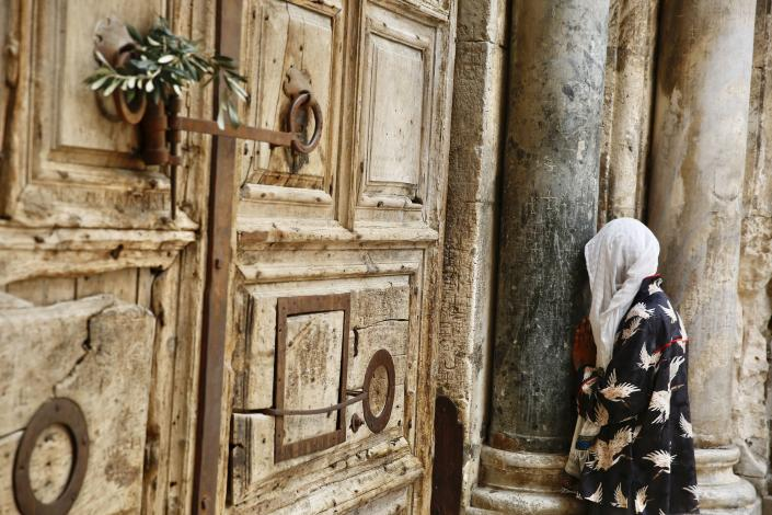 A woman prays in front of the closed Church of the Holy Sepulchre, a place where Christians believe Jesus Christ was buried, as a palm hangs on the door, in Jerusalem's Old City, Sunday, April 5, 2020. The traditional Palm Sunday procession was cancelled due to restrictions imposed to contain the spread of the coronavirus. (AP Photo/Ariel Schalit)