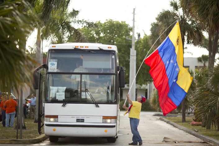 Guillermo Beltran waves his country's flag as Venezuelans from South Florida prepare for their bus trip to Washington, Thursday, May 8, 2014, in Doral, Fla. They are rallying to ask the Congress and President Barack Obama to impose economic sanctions and travel restrictions to the Venezuelan government officials because of presumed human right violations in the South American country. Organizers said they expect Venezuelans from 19 states will meet in Washington on Friday to demonstrate in front of the White House, Congress and the Organization of American States. (AP Photo/J Pat Carter)