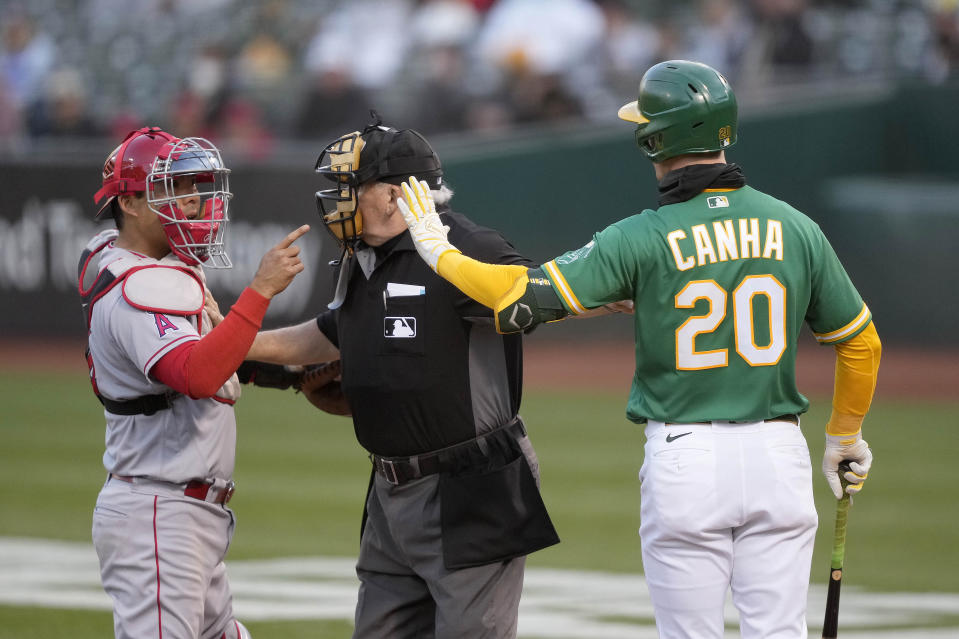 Los Angeles Angels catcher Kurt Suzuki, left, and Oakland Athletics' Mark Canha (20) argue as umpire Larry Vanover, center, gets between them during the third inning of a baseball game Friday, May 28, 2021, in Oakland, Calif. (AP Photo/Tony Avelar)