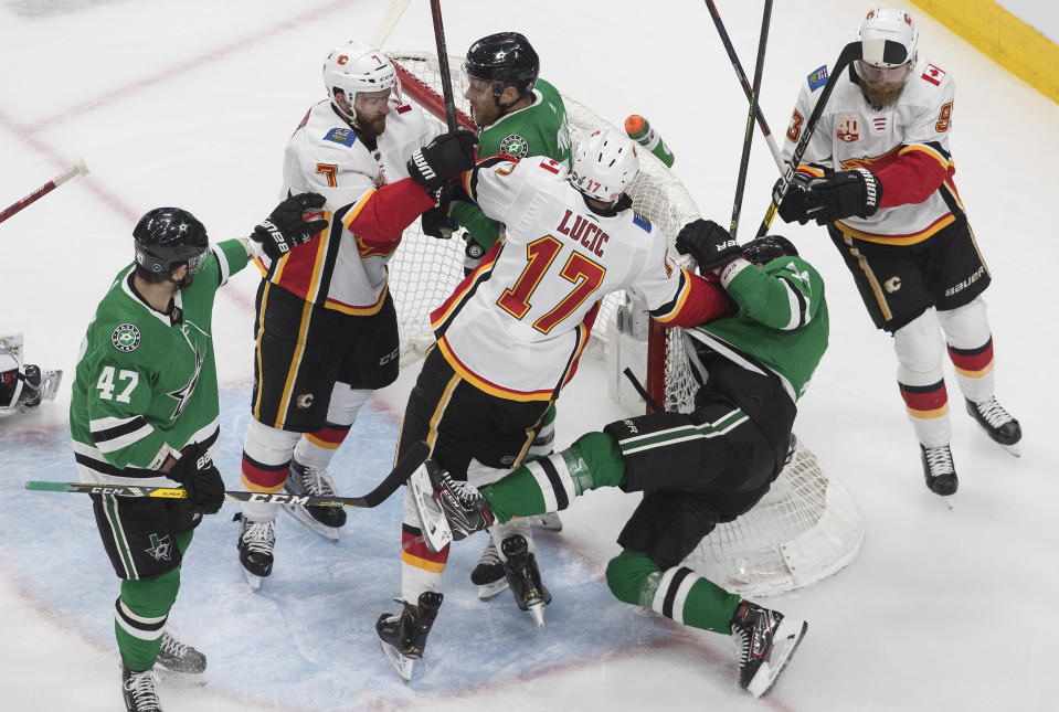 Calgary Flames' Milan Lucic (17) shoves Dallas Stars' Jamie Benn (14) against the net during a scrum in the second period in Game 5 of an NHL hockey first-round playoff series, Tuesday, Aug. 18, 2020, in Edmonton, Alberta. (Jason Franson/The Canadian Press via AP)