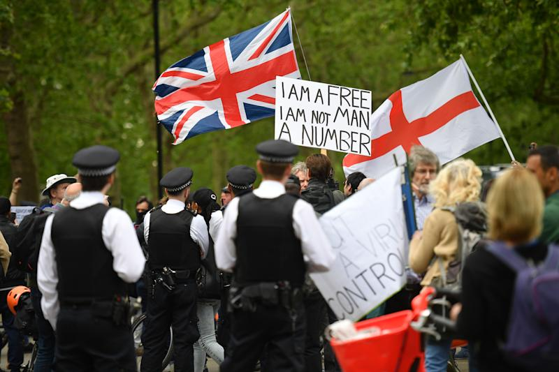 "Police attend an anti-coronavirus lockdown demonstration with protesters holding a Union Flag (L), a Flag of St George (R) and a placard that reads ""I am a free man, I am not a number"" in Hyde Park in London on May 16, 2020, following an easing of lockdown rules in England during the novel coronavirus COVID-19 pandemic. - Fliers advertising 'mass gatherings' organised by the UK Freedom Movement to oppose the government lockdown measures and guidelines put in place to halt the spread of coronavirus in parks around the UK calling for attendees to bring a picnic and music have been circulating on social media. People are being asked to ""think carefully"" before visiting national parks and beaches on the first weekend since coronavirus lockdown measures were partially eased in England. (Photo by JUSTIN TALLIS / AFP) (Photo by JUSTIN TALLIS/AFP via Getty Images)"