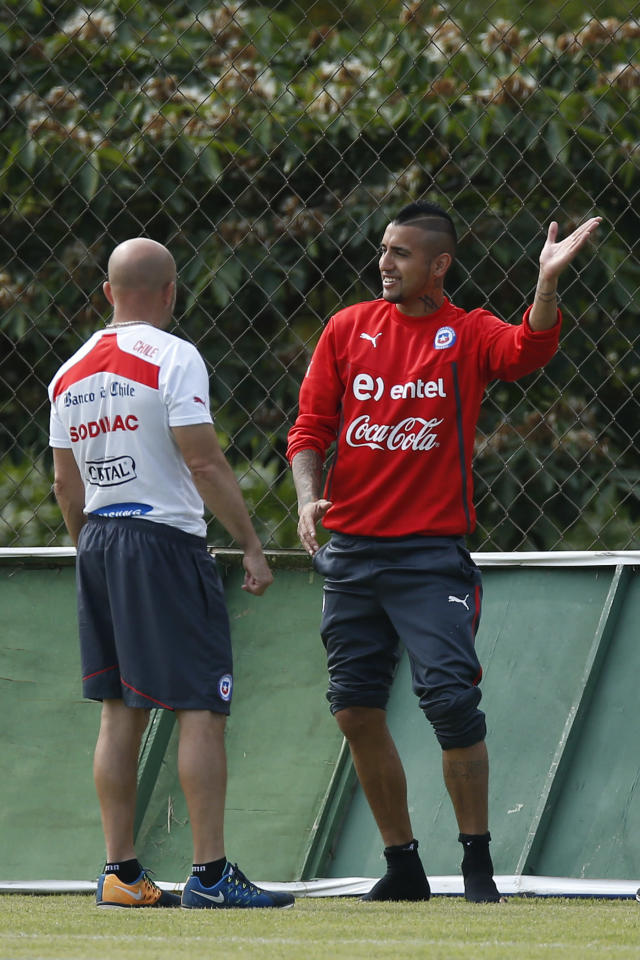 Chile's Arturo Vidal, right, talks with head coach Jorge Sampaoli during a training session at Toca da Raposa 2 center in Belo Horizonte, Brazil, Thursday, June 19, 2014. Chile plays in group B of the 2014 soccer World Cup. (AP Photo/Victor R. Caivano)