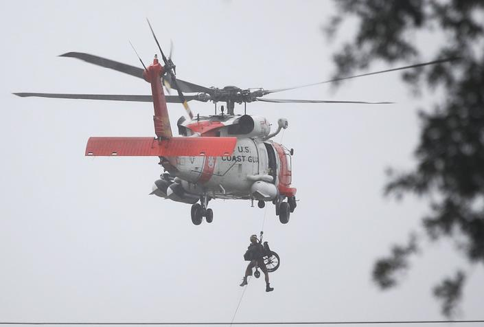 A Coast Guard helicopter hoists a wheel chair on board after lifting a person to safety in Houston.