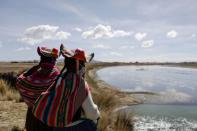 Women stand on the shores of the Coata river in the Carata peasant community, in Puno